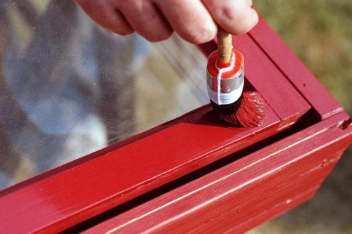 Nærbilde av et vindu som blir malt rødt
