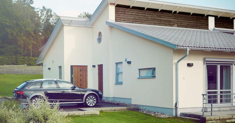 Hvit murhus med bil parkert foran