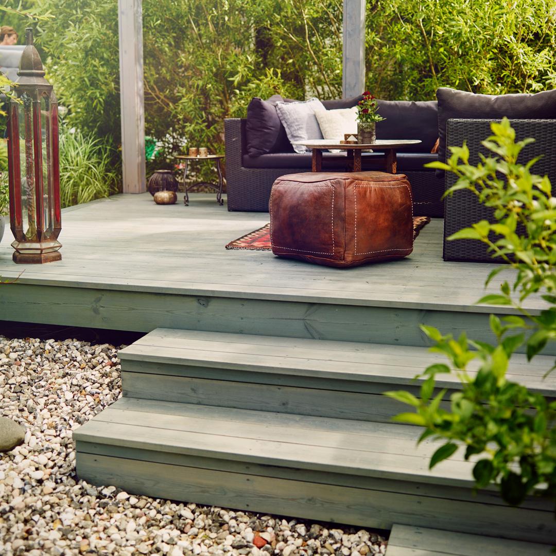 terrassegulv med flotte møbler og frodig hage