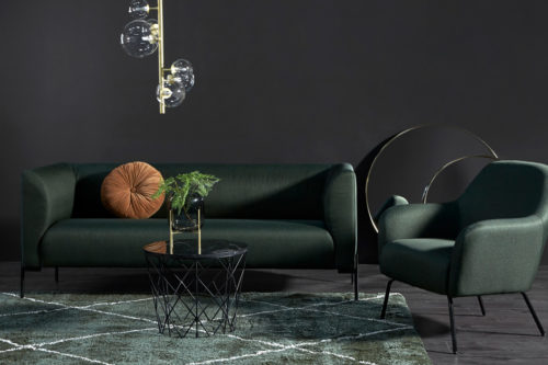 Grønn sofa med stol i en stue med sort farge på veggen og grønt teppe under bordet