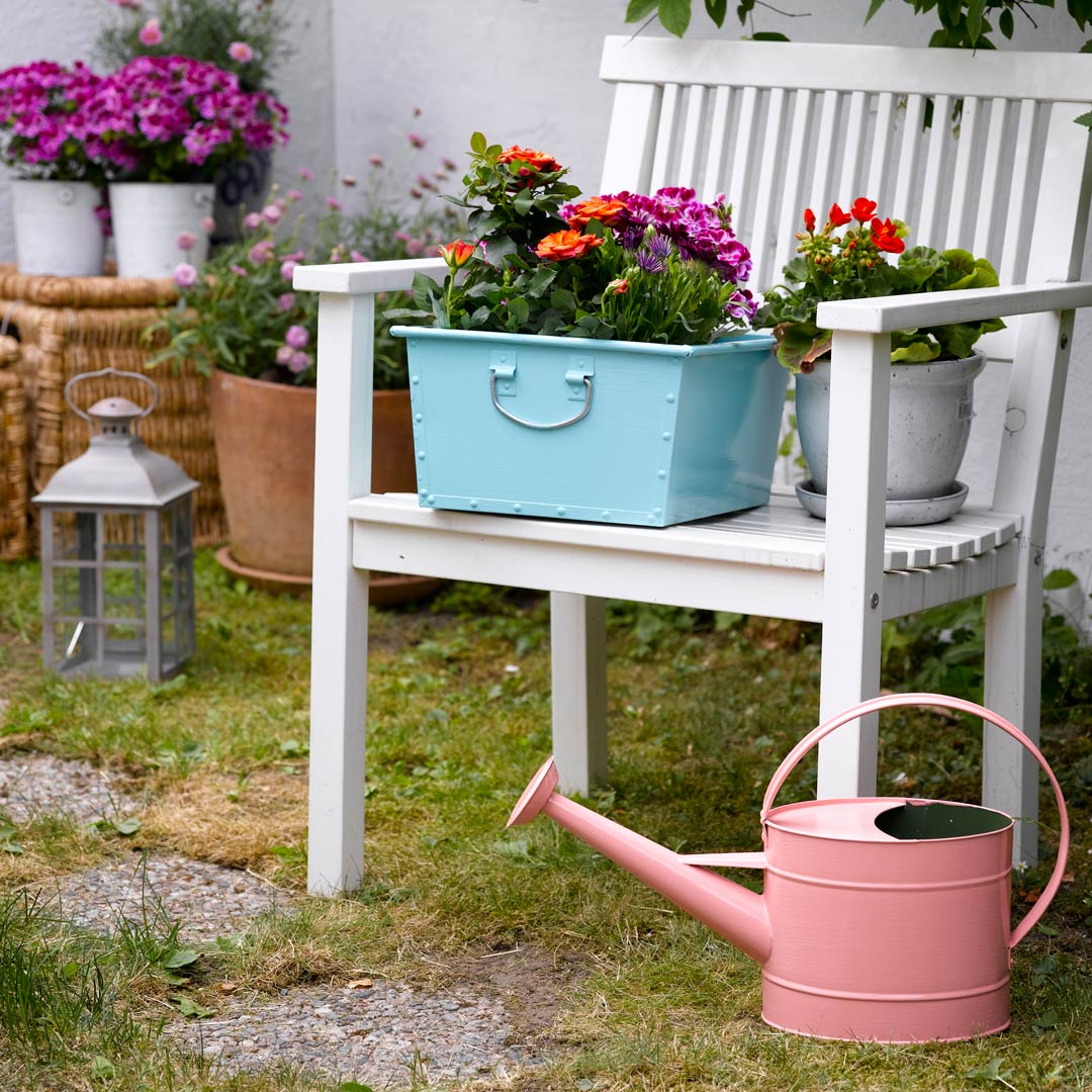 metall bakke malt i turkis på en hvit hagestol og en kanne malt i rosa stående ved siden